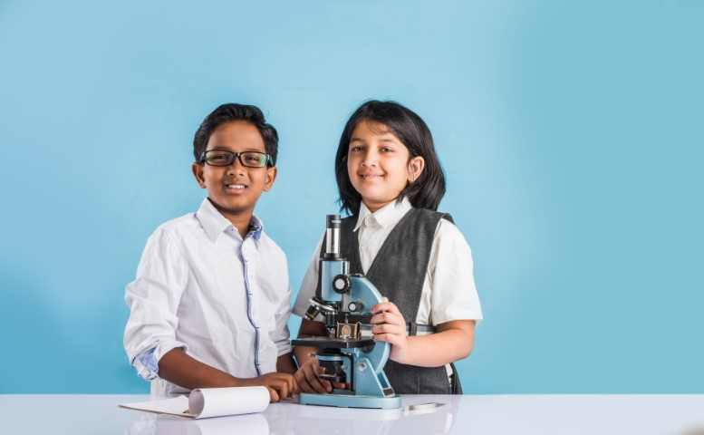 two children standing with a microscope